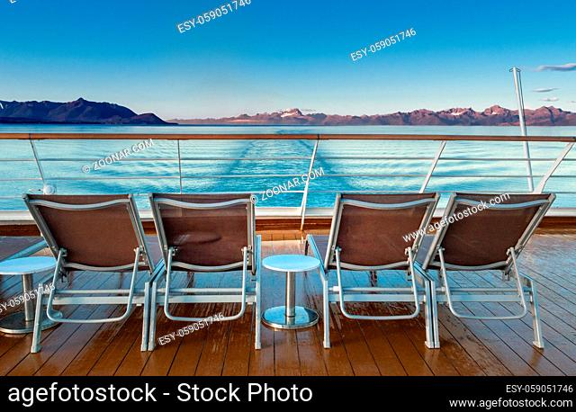 Early morning ocean view of empty plastic deck lounge chairs in the clear and damp early morning air at sunrise on a cruise ship