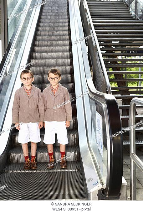 Twin brothers standing on escalator