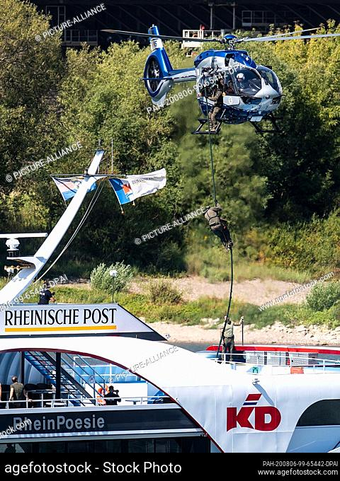 06 August 2020, North Rhine-Westphalia, Leverkusen: During an exercise, members of a special police task force (SEK) rappel from a helicopter to a pleasure boat...