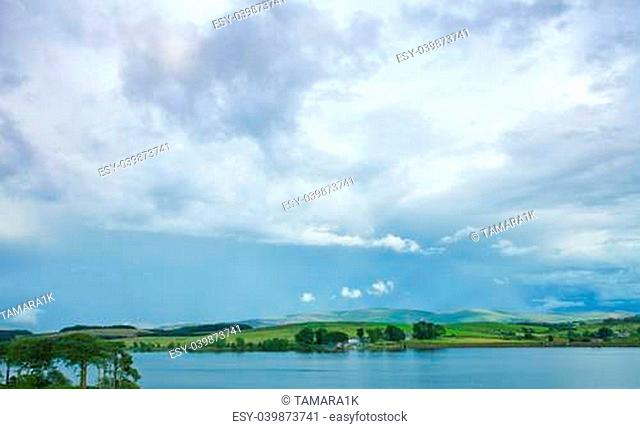 scottish landscape with clouds over lake