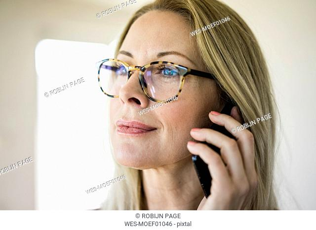 Portrait of blond mature woman wearing glasses on the phone