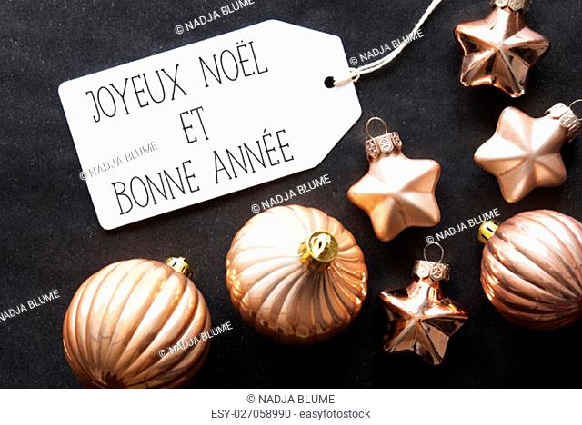 Label With French Text Joyeux Noel Et Bonne Annee Means Merry Christmas And Happy New Year. Bronze Christmas Tree Balls On Black Paper Background