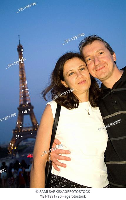 Couple smiling in front of Eiffel Tower at dusk, Paris, France