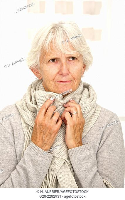 Senior woman in grey feeling cold and wrapping herself in a woolen scarf