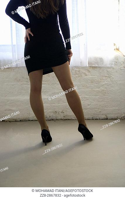 Rear view close up of a woman wearing a dress and high heels shoes standing by the window