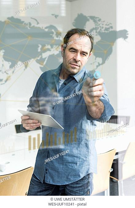 Businessman with tablet touching glass pane with world map and global network in office
