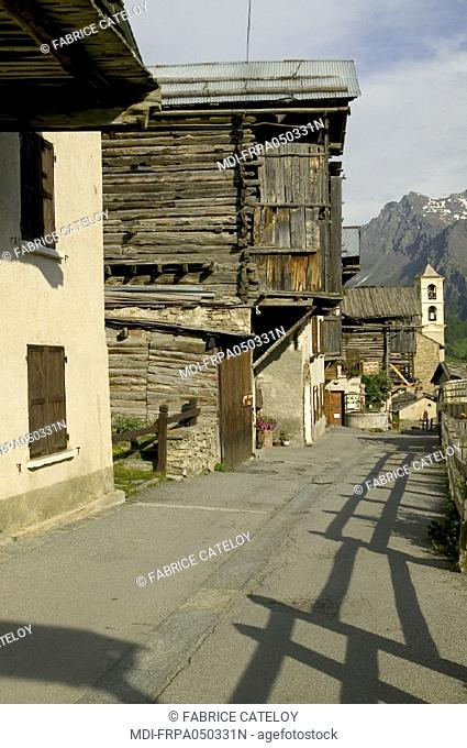St Veran, the highest village in Europe, 2042 meters - Traditional house in stone, surmounted by a part in larch wood to stock the fodder - In the background