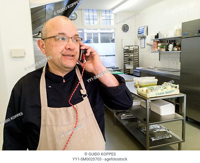 Tilburg, Netherlands. Pro chef making an order by phone for new and fresh ingredients for his dishes