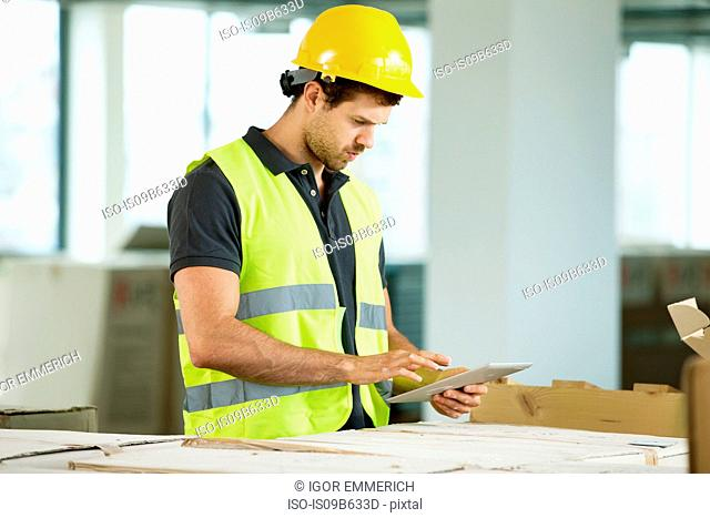 Man wearing hi vis vest, standing in newly constructed space, looking at digital tablet