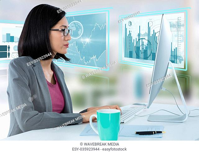 Businesswoman at desk with computer and bar charts interface graphics screens
