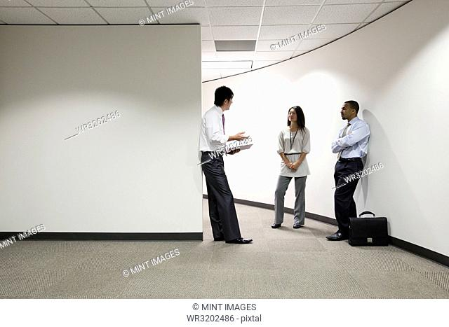 A mixed race group of three businesspeople standing and talking in an office hallway