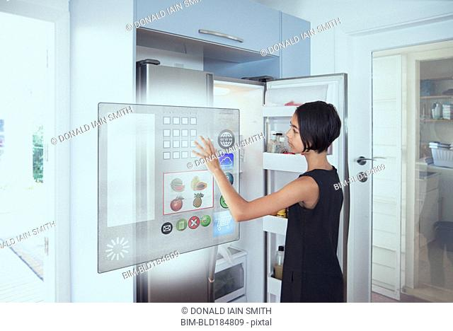 Mixed race girl using hologram refrigerator touch screen in kitchen
