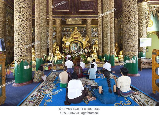 Devotees prying in the Temple with the Gautama Buddah image, Shwedagon pagoda, Yangon, Myanmar, Asia