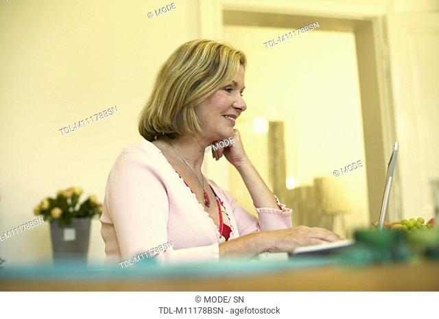 A woman at home working on a laptop