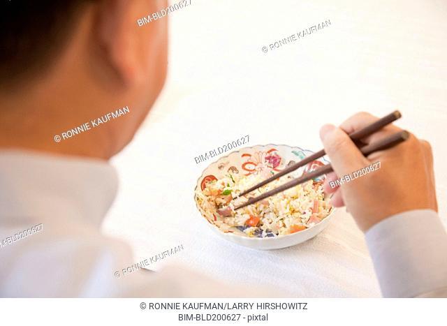 Asian man eating with chopsticks