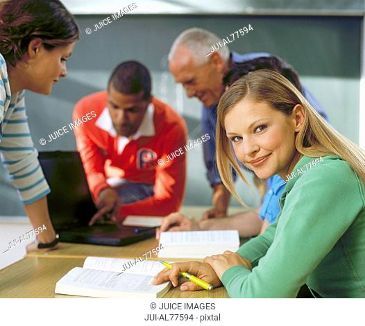 Woman looking away while teacher is teaching other students