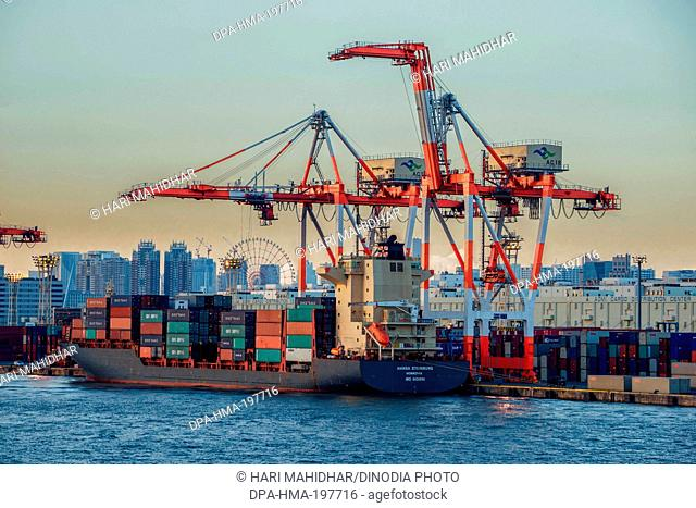 Loading containers on cargo ship at tokyo, harbour, japan