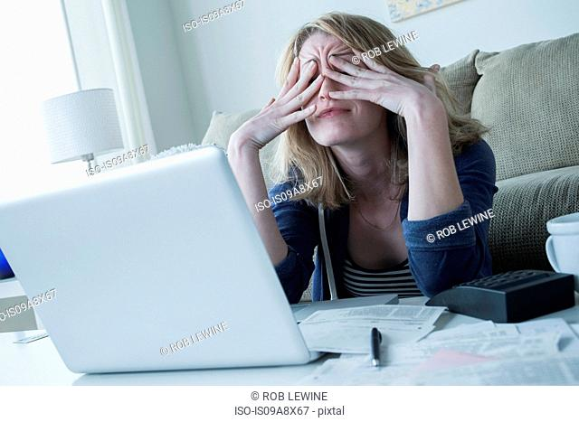 Stressed young woman rubbing eyes