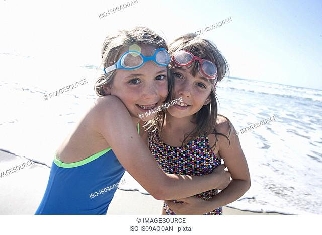 Portrait of twin sisters hugging on beach, Del Mar, California, USA