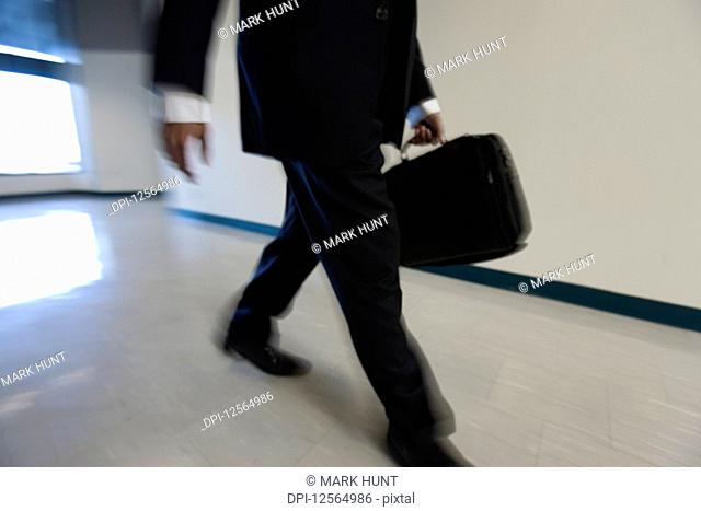 A young man walking in corridor holding briefcase