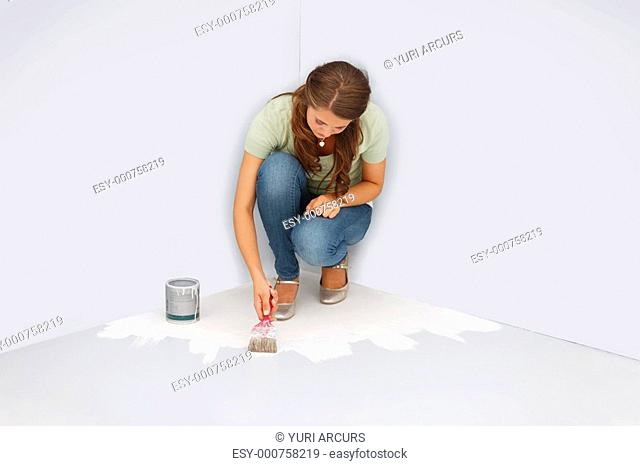 Young female painting the floor grey in color, trapped in the corner