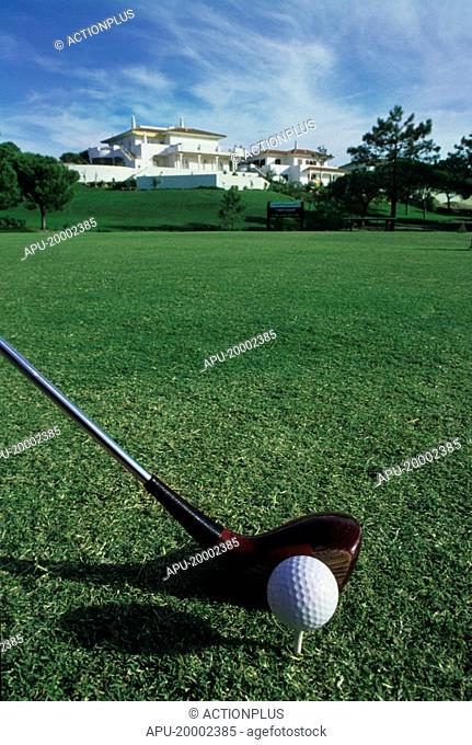 View of golfer about to strike ball with a wooden club