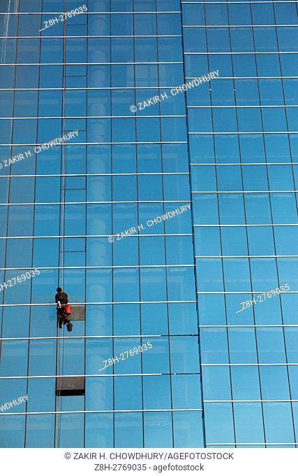 DHAKA, BANGLADESH - DECEMBER 03 : A labor clean the glass-wall of a high-rise building in Dhaka, Bangladesh on December 03, 2016