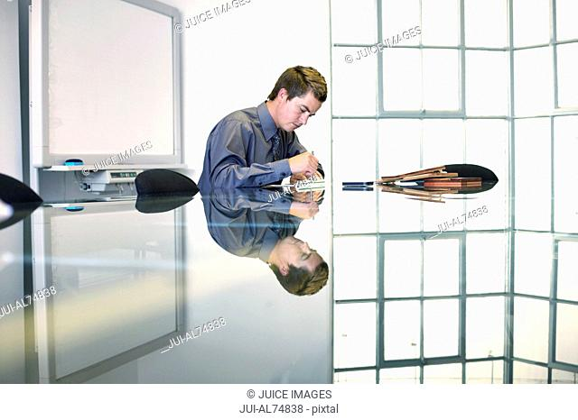 View of a young businessman writing some notes on a conference desk