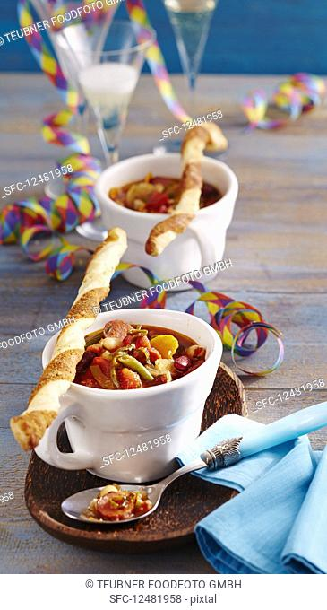 Spicy bean soup with sausages served with yeast dough and puff pastry Parmesan sticks