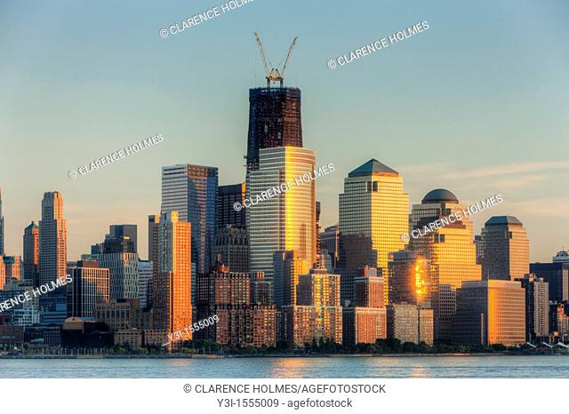 The sunset colored sky is reflected off of the building facades in lower Manhattan, including the World Financial Center and Battery Park City
