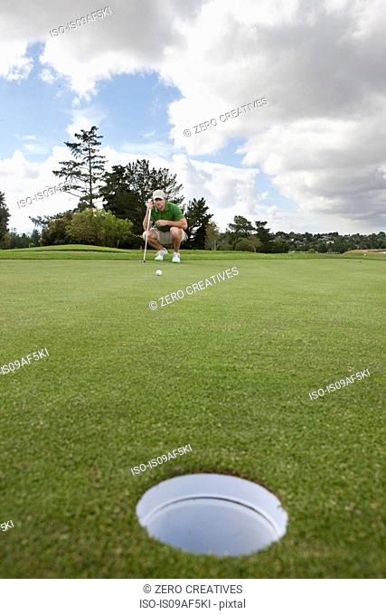 Young male golfer lining up the ball on the green