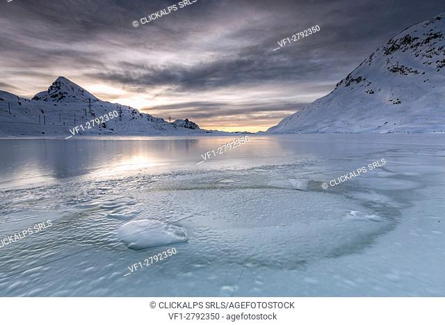The smooth ice and choppy splits are enhanced by a dark sky clouded by fanciful glazes. White Lake. Bernina Pass. Canton of Graubuenden. Engadine