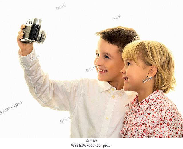 Smiling brother and sister taking a selfie with old-fashioned camera