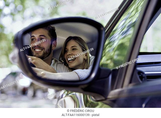 Reflection of couple in wing mirror