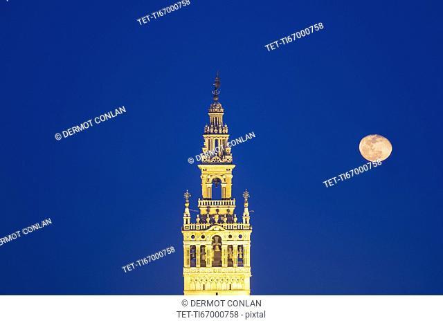 Spain, Seville, Giralda with full moon at dusk