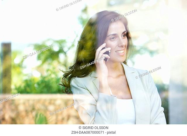 Businesswoman looking out of window from office while using cell phone