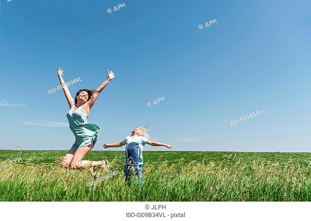 Mother and son jumping for joy in field