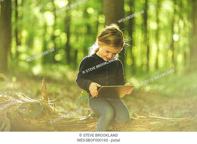 Girl in forest using digital tablet