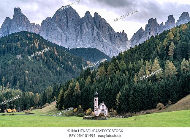 St. Johann in Ranui - a small church with onion tower in front of the Dolomite mountais Geisler massif in Santa Maddalena, Italy