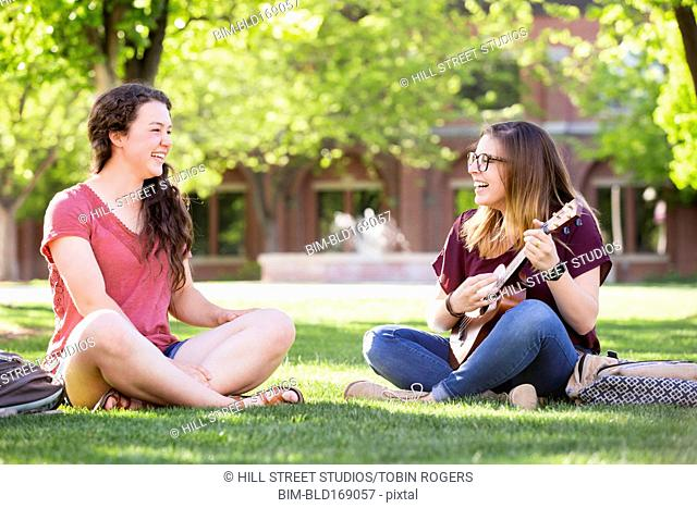 Students playing ukulele on college campus