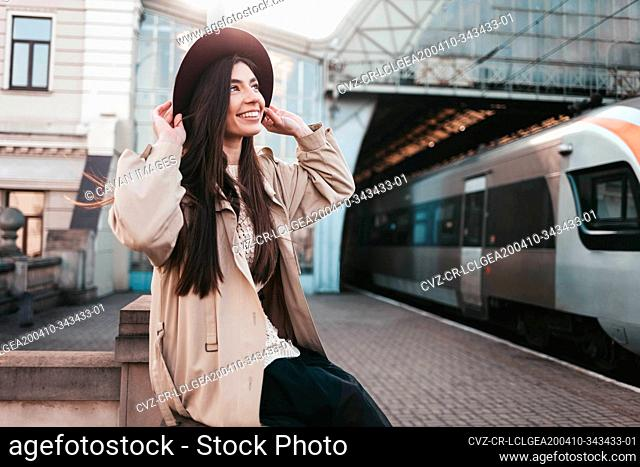 Smiling girl in hat at train station waiting for train departure