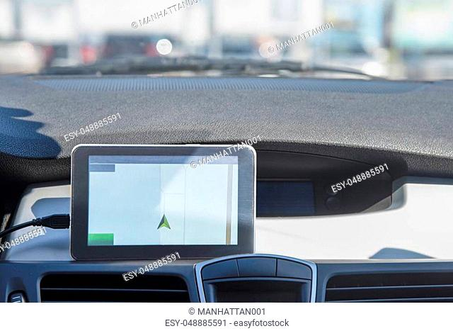 A car with a Navigator is located in the street Parking. View from inside the car
