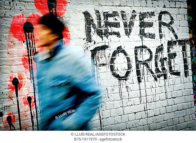 Never Forget graffiti, with man in motion in East London, London, England, UK