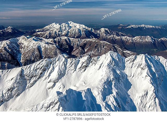 Flying high above the Orobie Alps after a heavy snowfall. In the background the two Grigne, in the foreground the peaks of Lesina valley Valtellina, Sondrio