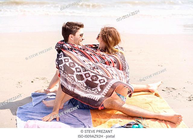 Couple on beach wrapped in blanket, Coney island, Brooklyn, New York, USA