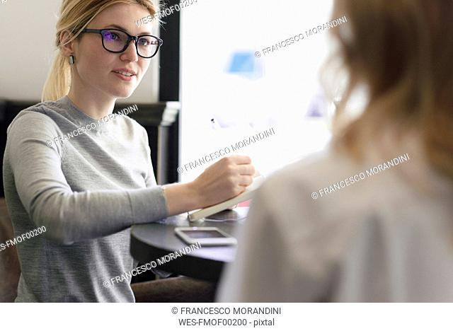 Businesswoman with notebook looking at colleague