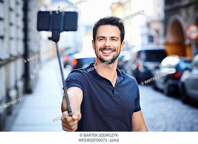 Man taking photo with smartphone mounted on selfie stick