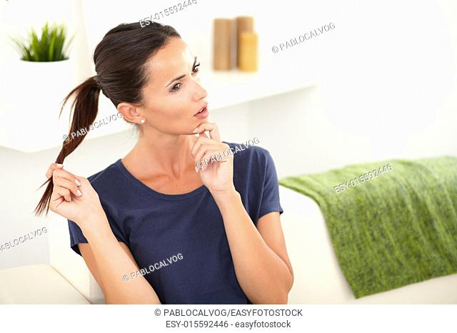 Beautiful woman wondering while sitting at home with one hand in her hair