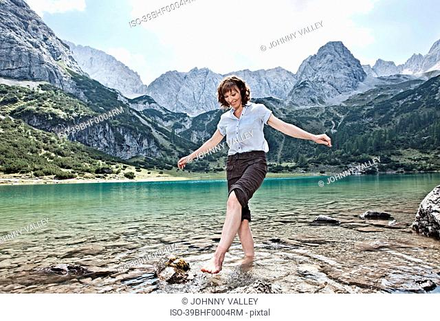 Woman in bare feet playing in lake