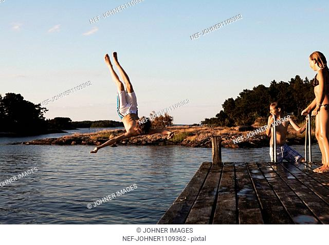 Teenage boys and girl jumping into water from pier